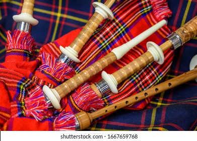 Scottish folk antique musical instrument bagpipes and colorful tartan fabric close up