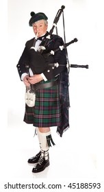 Scottish highlander wearing kilt and playing bagpipes