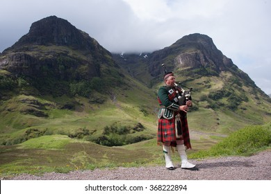 SCOTTISH HIGHLANDS - JUNE 15: Piper in traditional Scottish outfit plays on bagpipes in somewhere in Scottish Highlands, United Kingdom on June 15, 2013.