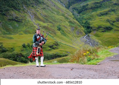 SCOTTISH HIGHLANDS - SEPTEMBER 24, 2015: Piper in traditional Scottish outfit plays on bagpipes in Scottish Highlands. In the background of the mountain. Cloudy autumn day.