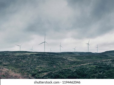 Scottish Landscape with Wind Turbines - view of wind turbines dotted along a bleak, barren landscape in the Scottish wilderness.