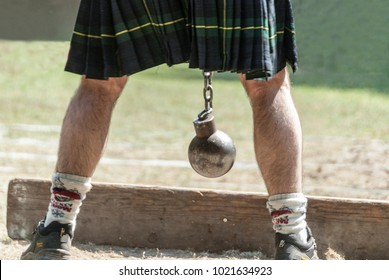 Scottish person with kilt and metal ball between his legs