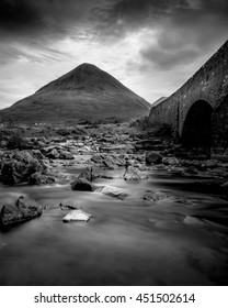 Scottish river with rocks and hill in background and bridge on side with stormy overcast clouds in black and white