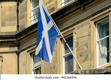 The Scottish Saltire flag on a flagpole outside a sandstone building in Edinburgh, Scotland.