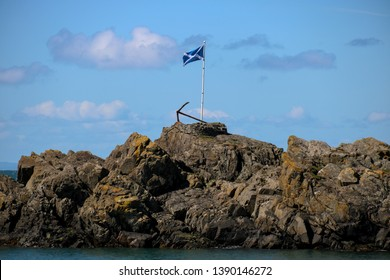 Scottish saltire flag and rusting anchor at Portpatrick harbour in southern Scotland
