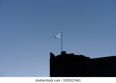 The Scottish Saltire flying against a blue sky over Doune Castle in Scotland