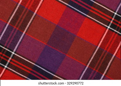 Scottish tartan pattern. Red and purple plaid print as background. Colored lines and square pattern. Scottish checked fabric.