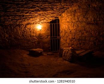 Scottish underground dungeon cells lit only by torchlight