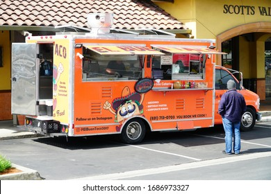 Scotts Valley, California, USA. March 26, 2020. A man waits for his lunch out side the El Buen Taco Taco Truck,