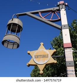 Scottsdale, Arizona/ USA - February 12, 2016:  Closeup sheriff's badge sign of historic Scottsdale beside pole with hanging lantern and wagon wheel.