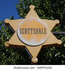 Scottsdale, Arizona / USA - February 2016:  Closeup of Marshall badge shaped Scottsdale sign against green tree foliage in background.