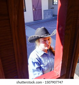 Scottsdale, Arizona/ USA - February 2016:  Looking out stagecoach window at cowgirl in black cowboy hat and working blue shirt helping tourists onto stagecoach.