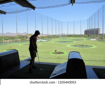 Scottsdale, Arizona / USA - May 20 2018: Silhouettes of people playing at TopGolf with targets in the background and blue sky