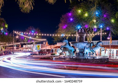 Scottsdale, AZ - February 9 2020: Traffic at night around Bob Parks' Bronze Horse Fountain in Old Town Scottsdale's 5th Avenue Shopping district.