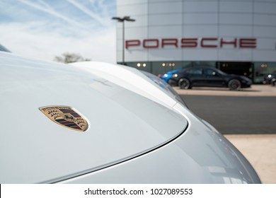 Scottsdale, AZ, USA - 17 February 2018: Logo of white Porsche 718 Cayman 2018 in front of Porshe store. Porsche AG is a German automobile manufacturer specializing in high-performance sports vehicles.