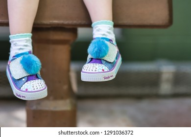 Scottsdale, AZ / USA - September 22, 2018: Close-up of legs of a little girl sitting outdoors on a bench wearing Twinkle Toes by Sketchers USA, an American lifestyle and performance footwear company