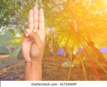 Scout honor hand gesture on blurred scouts camping background.