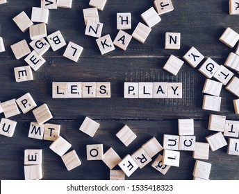 Scrabble letters on a wooden table spelling words LETS PLAY