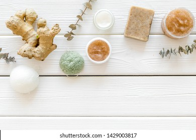 Scrabs and creams for natural cosmetic set with herbs and ginger on white wooden background top view mock-up