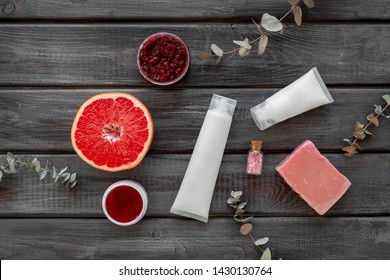 Scrabs, soap and creams for natural cosmetic set with herbs and grapefruit on wooden background top view