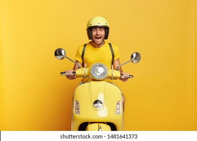 Scraed emotional driver poses on motorbike, drives long destination, has frightened look, screams from fear, wears yellow headgear, t shirt, carries rucksack on back, afraids of very high speed