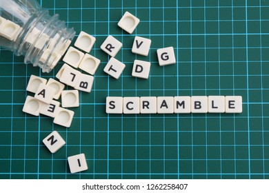 Scramble word made of square letter block on green square mat background.