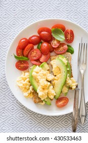 Scrambled eggs and avocado on whole grain toast. Concept of healthy breakfast.