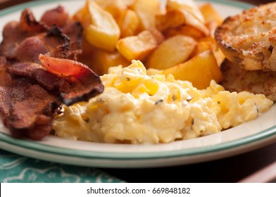 scrambled eggs, bacon, home fries and an english muffin breakfast