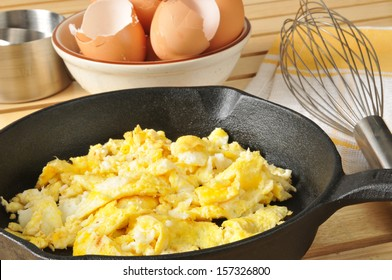 Scrambled eggs with brown egg shells in a bowl behind