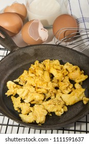 scrambled eggs in a cast iron pan and  whisk, eggshell, fresh egg