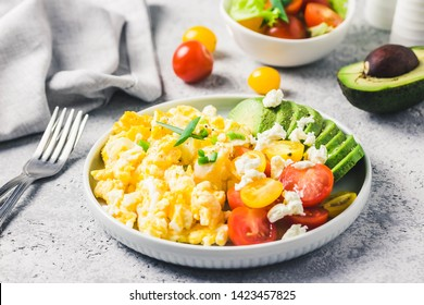 Scrambled eggs with cherry tomatoes , avocado feta cheese and olive oil.Selective focus, space for text.