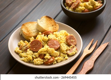 Scrambled eggs with chorizo slices and onion on plate with toasted baguette slices, wooden fork and knife on beside, photographed with natural light (Selective Focus, Focus one third onto the plate)