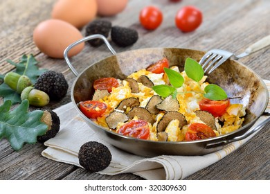 Scrambled eggs with fresh black truffles from France served in a frying pan
