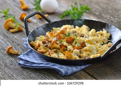 Scrambled eggs with fresh chanterelles in a serving pan on an old wooden table