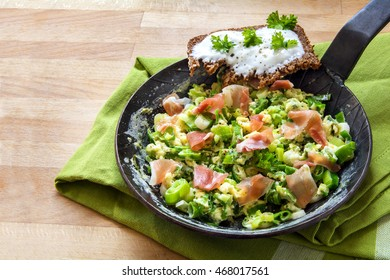 scrambled eggs with green onions and prosciutto in a black iron pan on green cloth and a wooden background with copy space