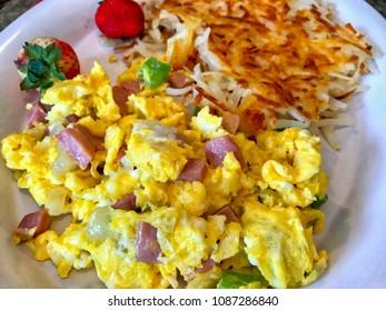Scrambled eggs with ham and herbs, closeup