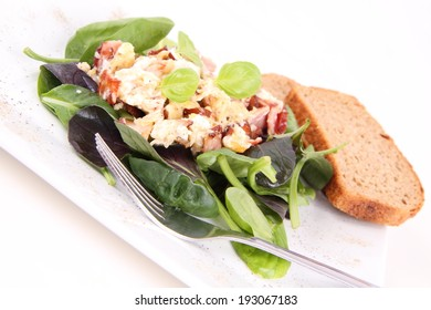 Scrambled eggs with ham on spinach, with wholemeal bread
