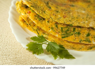 Scrambled eggs with herbs. Omelet on white plate
