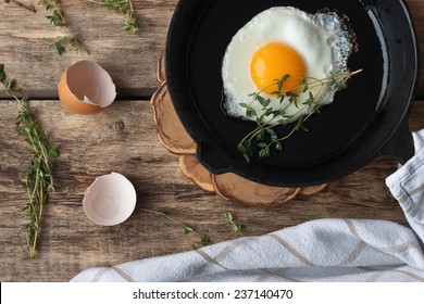 Scrambled eggs in an iron pan on the rustic wooden table