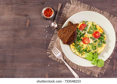 Scrambled eggs with kale and toast on wooden table. Top view with copy space.