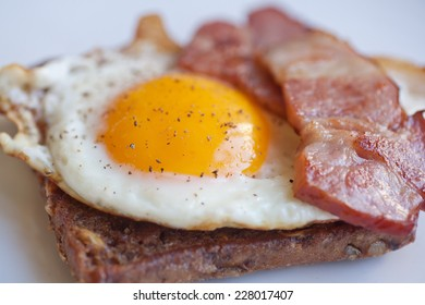 scrambled eggs on rye bread toast with bacon, close up