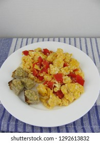 Scrambled eggs with red paprika and bread with homemade olive paste