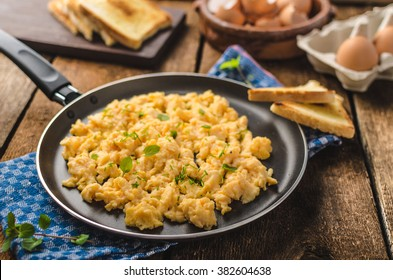 Scrambled eggs rustic style, with toast and herbs