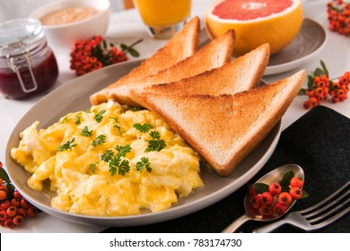 scrambled eggs with toast fruit juice jelly and peanut butter, morning, daylight, stone background
