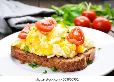 Scrambled eggs with tomato on bread, close up view.