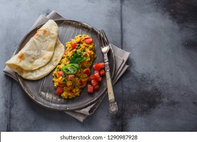 Scrambled eggs with tomatoes and chives on a plate, copy space