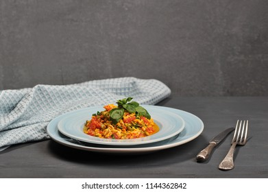 Scrambled eggs in Turkish menemen with tomatoes, green pepper and fresh herbs. Next to the plate are cutlery and a cloth slick. Gray background. Close-up.