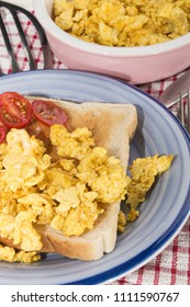 scrambled organic eggs on toast and sliced plum tomatoes
