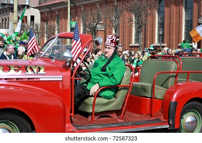 SCRANTON, PA - MARCH 14: A man drives an old red car as part of the Scranton St. Patrick's Day parade on March 14, 2009. Scranton holds one of the largest parades in the United States.