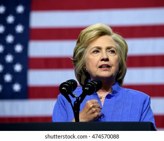 SCRANTON, PA, USA - AUGUST 15, 2016: Democratic presidential nominee Hillary Clinton in a blue suit speaks with the American Flag in the background at a campaign rally at Riverfront Sports.